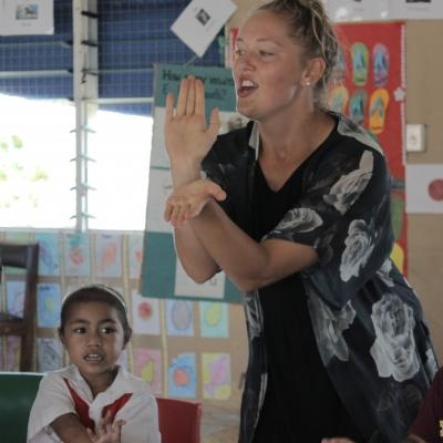 A volunteer in a village in Samoa teaches children at a school.